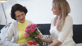 Young attractive daughter is visiting elderly mother, talking and giving beautiful bouquet of pink roses stock footage