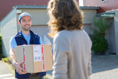 Young attractive delivery man on his way to customer Royalty Free Stock Image