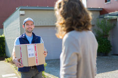 Young attractive delivery man on his way to customer Stock Images