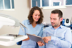 Young attractive dentist explaning his work to a patient Royalty Free Stock Image