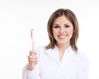 Young attractive dentist with a pink toothbrush Stock Photo