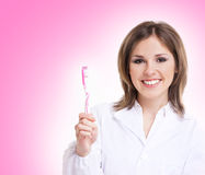 Young attractive dentist with a pink toothbrush Royalty Free Stock Image