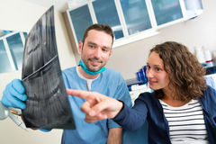 Young attractive dentist showing x-ray to patient Stock Image