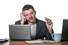 Young attractive depressed and frustrated businessman working at office computer desk desperate and overwhelmed feeling upset stock photo
