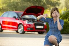 Desperate confused woman stranded with broken car engine crash accident calling on mobile phone Stock Photos