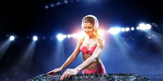Cute dj woman. Mixed media. Young attractive dj woman in bikini playing her music. Mixed media stock photo