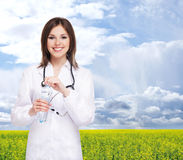 Young attractive doctor on a blue sky background Royalty Free Stock Images