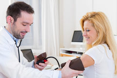 Young attractive doctor checking patient's blood pressure Stock Images