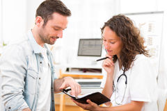 Young attractive doctor dating next appointment Stock Photography