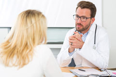 Young attractive doctor listening his patient Royalty Free Stock Image