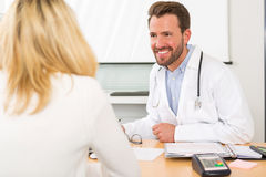 Young attractive doctor listening his patient Stock Images