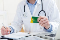Young attractive doctor taking health insurance card Royalty Free Stock Image