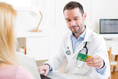 Young attractive doctor taking health insurance card Stock Photos