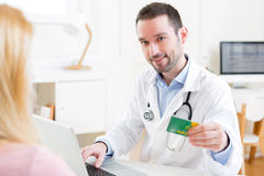 Young attractive doctor taking health insurance card Stock Photography