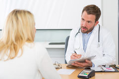 Young attractive doctor taking notes while patient speak Stock Images
