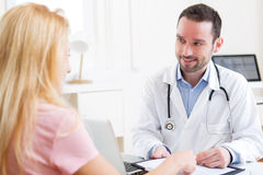 Young attractive doctor taking notes while patient speaking Royalty Free Stock Photography