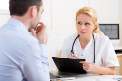 Young attractive doctor taking notes while patient speaking Royalty Free Stock Images
