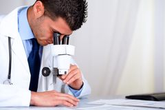 Young attractive doctor working with a microscope Stock Image