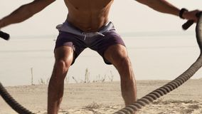 Young Attractive Dynamic Handsome Man Battling Ropes. Cross Power Training. Close-up Young Shirtless Muscular Man Training with Battle Ropes on the Beach Against stock video