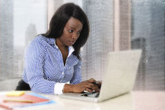 Young attractive and efficient black ethnicity woman sitting at business district office computer laptop desk typing Stock Photography