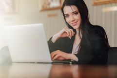 Young attractive emotional girl in business-style clothes sitting at a desk on a laptop and phone in the office or auditorium royalty free stock image