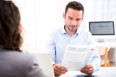 Young attractive employer analysing resume of woman Stock Images