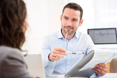 Young attractive employer analysing resume of woman Stock Photo