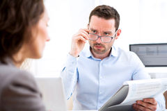 Young attractive employer analysing resume of woman Royalty Free Stock Images