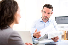 Young attractive employer analysing resume of woman Royalty Free Stock Photos