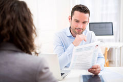 Young attractive employer analysing resume of woman. View of a Young attractive employer analysing resume of woman stock photography