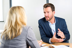 Young attractive employer doing a job interview to a woman Royalty Free Stock Photography