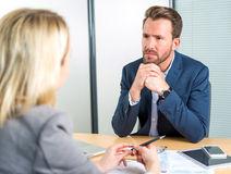 Young attractive employer doing a job interview to a woman Royalty Free Stock Images