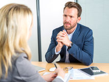 Young attractive employer doing a job interview to a woman stock image