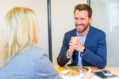 Young attractive employer doing a job interview to a woman Royalty Free Stock Image