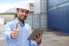 Young Attractive engineer using tablet on the dock Royalty Free Stock Image