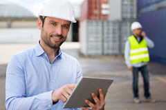 Young Attractive engineer using tablet on the dock Royalty Free Stock Photos