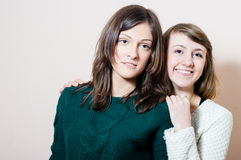 2 young attractive enjoyable women having fun friendly hugging in knitwear happy smiling & looking at camera. Portrait of two young beautiful ladies having fun royalty free stock photography
