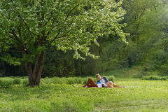 Young attractive european couple with small dog is getting rest on blanket in some summer park at warm sunny day. Beautiful woman. Young attractive european Stock Photography