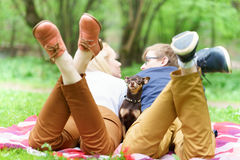 Young attractive european couple with small dog between them is getting rest on blanket in some summer park at warm sunny day. Stock Photos