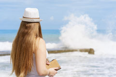 Young attractive european woman with notepad and pen is staying close to beach of blue tropical sea on background of splashing str royalty free stock images
