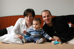 Young attractive family. A young attractive family on the bed - mother, father and baby boy with a toy Royalty Free Stock Photo