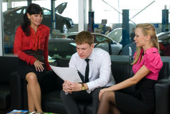 Young attractive family in car shop Royalty Free Stock Photos