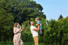 Young attractive family playing with child in a meadow and drinking juice Royalty Free Stock Images