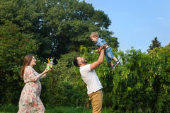 Young attractive family playing with child in a meadow and drinking juice Stock Image