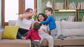 Young attractive family with two kids in the living room sitting on the sofa they smiling large playing together and