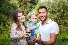 Young attractive family walking in a meadow and drinking juice Royalty Free Stock Image