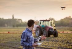 Farmer driving drone above field stock photography