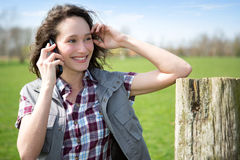 Young attractive farmer in a field using mobile phone Royalty Free Stock Photography