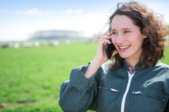 Young attractive farmer in a field using mobile phone Royalty Free Stock Photo