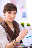 Young attractive fashion designer standing by desk Royalty Free Stock Image